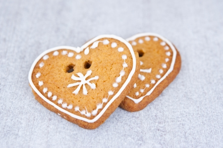Two sweet gingerbread hearts, decorated with icing, on a wooden table photo