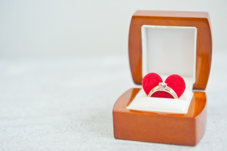 Gold ring with a diamond, a red heart, in a wooden jewelry box on a white wooden table photo