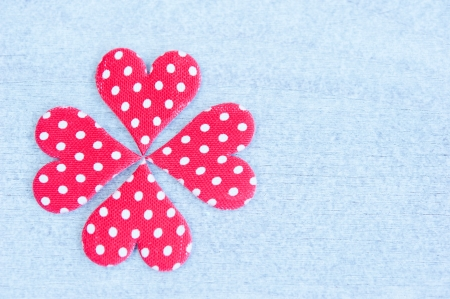 Of four red hearts with white polka dots lined quatrefoil, wooden table photo