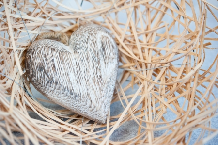 Vintage wooden heart in a nest of straw on a wooden table photo