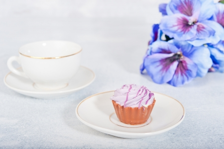 A cup of tea, a small cake in the background purple flowers Stock Photo - 17688631