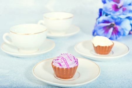 Two cups of tea, two small cakes in the background purple flowers Stock Photo - 17688634