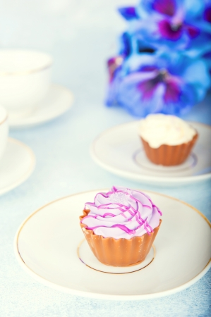 Two small cake, two cups of tea, purple flowers, vertical frame Stock Photo - 17688635