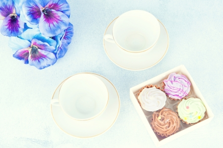 two cups of tea, a box with a small cake, purple flowers Stock Photo - 17688639