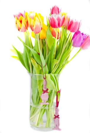 bouquet of colorful tulips in a vase, decorated with wooden figures of hares Stock Photo