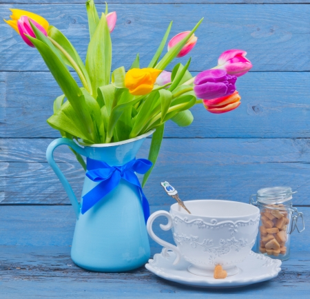 Bouquet of colorful tulips in a blue jug, next cup of tea on blue wooden table photo