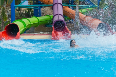 three slides at the water park rolls out of the middle child, splashing water photo