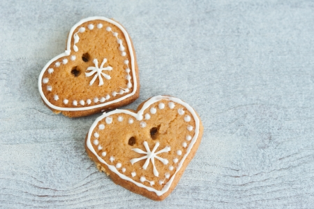 Two Christmas gingerbread heart, decorated with icing on a wooden table photo