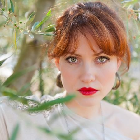 pelo rojo: Retrato de una chica europea con el pelo rojo, ojos verdes y labios de color rojo contra la rama de olivo