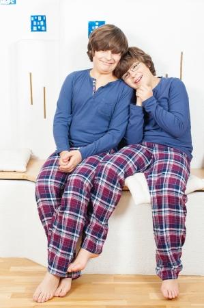 bedsheets: Due boy europea in pigiama, seduta sul fuoco, con la testa sulla spalla di uno secondo Archivio Fotografico