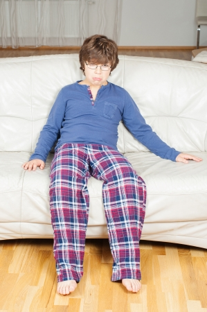 European boy in pajamas sitting on the couch sad