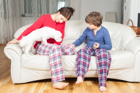 European woman with son in pajamas on the couch, next to a small white dog photo