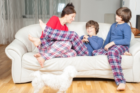 European woman with sons in pajamas on the couch, next to a small white dog photo