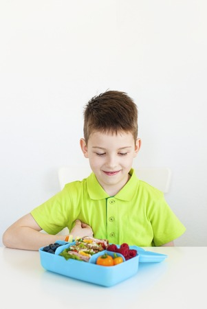 One young boy sitting at the table and looking at his lunch box. white background. Stock Photo