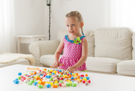 Cute funny little girl in a colorful dress playing with colorful toys.