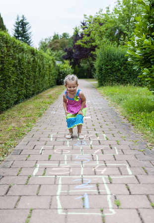 Cute cheerful girl playing hopscotch on playground outside