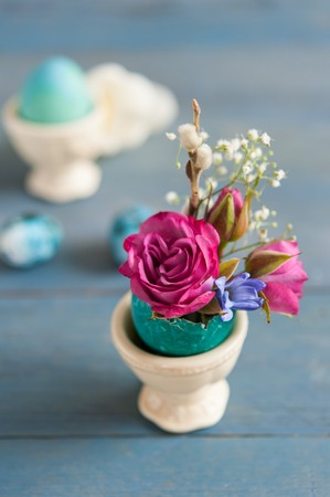 Bright Easter eggshell with flowers in stand on wooden background.