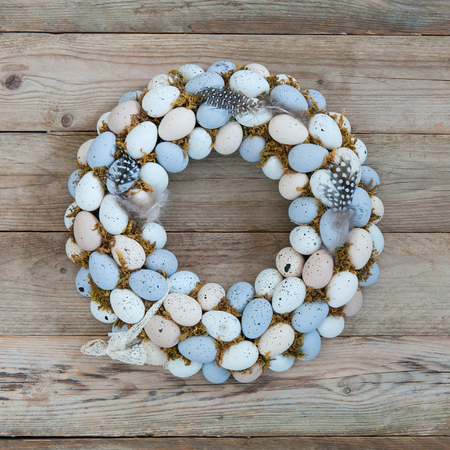 Delicate Easter wreath on the door of quail eggs on a wooden background.