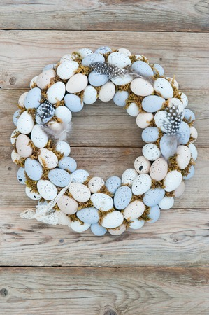 Delicate Easter wreath on the door of quail eggs on a wooden background Banco de Imagens