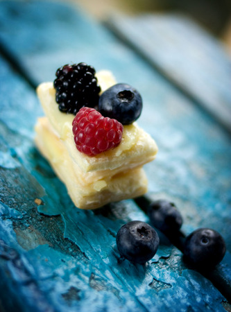 Flaky cake. Delicate flaky cake with raspberries and blueberries. photo