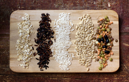 Several kinds of grains are together on the plank photo
