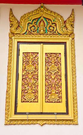 Ancient Golden carving wooden door of Thai temple in Bangkok, Thailand.  photo