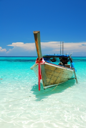 A boat on clear blue sea in a sunny day photo