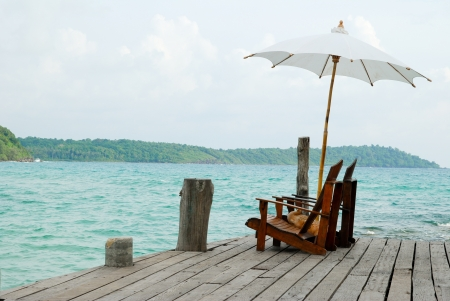 A pair of chair and an umbrella nearby the sea photo