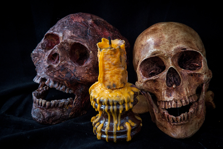 old photo: Couple of skull and candle in black background. Stock Photo