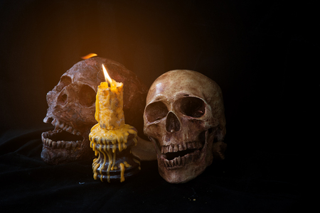 Couple of skull and candle in black background. Stock Photo