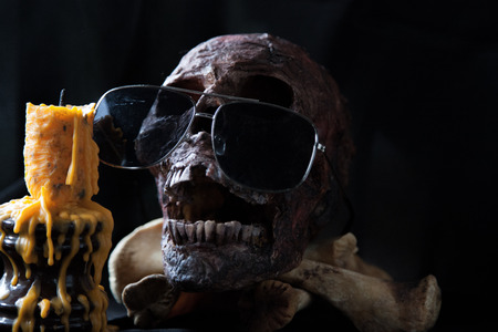old photo: Skull with sunglasses and candle in black background. Stock Photo