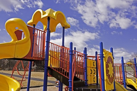 A new playground slide set under a blue sky awaits the warm weather and the children Stock Photo