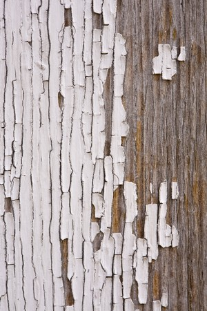 A section of wood showing a section of paint peeling, chipping, and needing a lot of repair