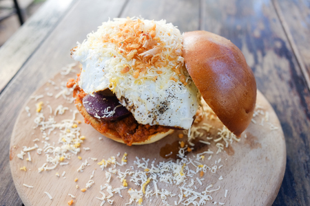Fusion hamburger with fired pork and fired egg served on wooden plate