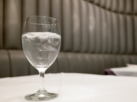 vaso de precipitado: Tall glass fill by water and ice put on whit surface table in resturant