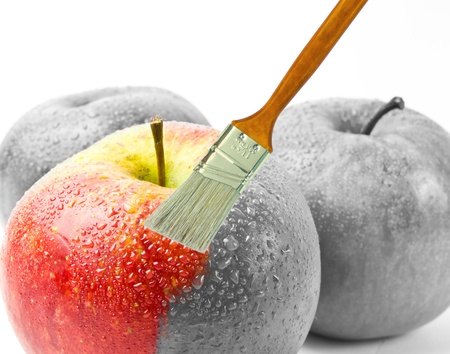paintbrush painting a fresh red wet apple which is partly black and white and partly colored