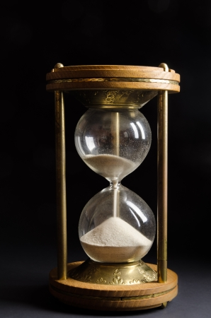 reloj de arena: Antiguo reloj de arena sobre fondo negro