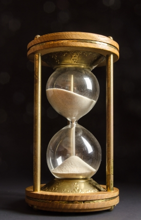 Old hourglass on black background