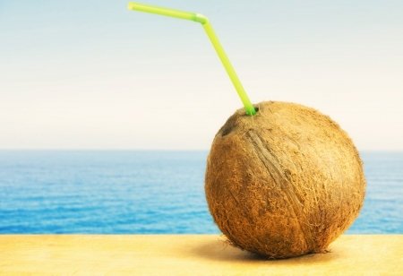 Coconut with drinking straw on a beach at the caribbean sea  Stock Photo