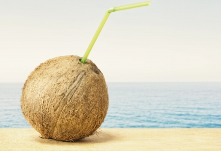 Coconut with drinking straw on a beach at the caribbean sea  photo