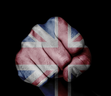 british flag: Low key picture of a fist painted in colors of united kingdom flag