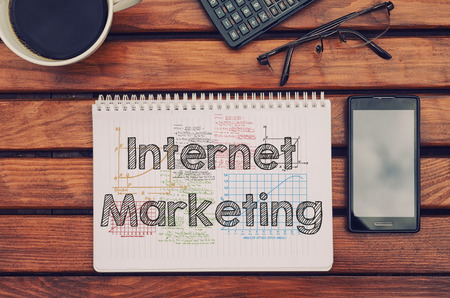 Notebook with text inside Internet Marketing on table with coffee, mobile phone and glasses.