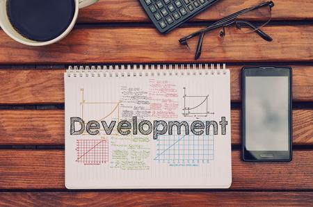 Notebook met tekst binnen - Ontwikkeling op tafel met koffie, mobiele telefoon en een bril. Stockfoto
