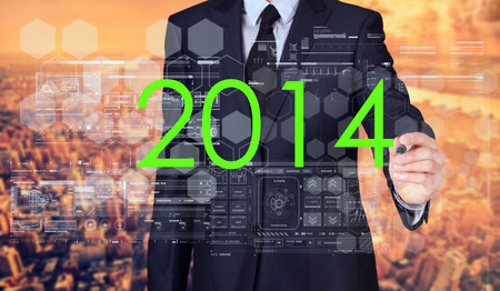 businessman writing 2014 and drawing some sketches with modern city in background Stock Photo