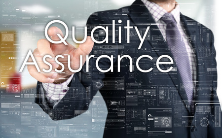quality: The businessman is choosing Quality Assurance from touch screen