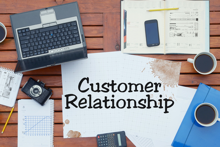 Notebook with text inside Customer Relationship on table with coffee, notebook and pencils