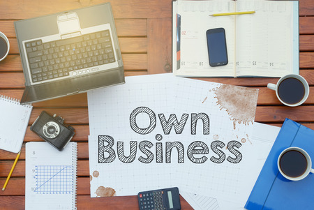 own: Notebook with text inside Own Business on table with coffee, laptop PC and crumpled sheets