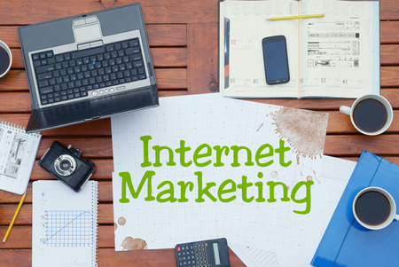 adwords: Notebook with text inside Internet Marketing on table with coffee, mobile phone and glasses.
