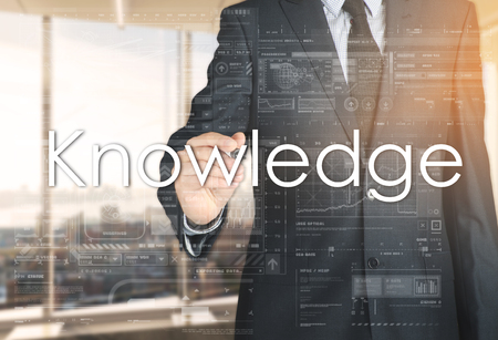 the businessman in the office is writing on the transparent board: Knowledge Stock Photo
