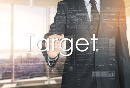 the businessman in the office is writing on the transparent board: Target